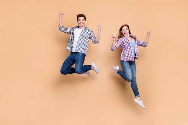 성공적인 승리를 축하하는 v 기호 기호를 보여주는 높은 점프 두 사람이 미친 여자 남자의 전체 길이 사진 캐주얼 격자 무늬 청바지 옷 격리 된 베이지 색 배경