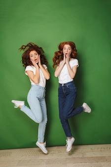 Фотография в полный рост двух удивленных рыжих девушек 20-х в белых футболках и джинсах, трогающих щеки с поднятыми ногами, изолированные на зеленом фоне