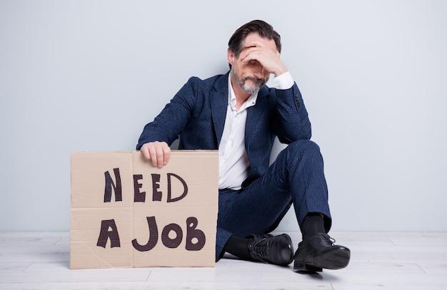 Полная фотография несчастного разочарованного работника зрелого парня, потерявшего работу без работы, мужчина держит картонный плакат, искать работу, сидеть на полу, скрывать глаза, смотреть, носить, синий костюм, туфли, изолированный серый фон