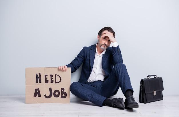 Полная фотография расстроенного разочарованного работника зрелого парня, потерявшего работу, безработный мужчина, держащий картонный плакат, необходимость работы, сидение на полу с портфелем, поиск офисной одежды, костюм, обувь, изолированный серый фон