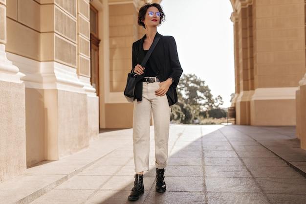 外でポーズをとっている軽いズボン、ブーツ、ジャケットの女性の全身写真。黒のハンドバッグと眼鏡を持った魅力的な女性が通りで微笑む。