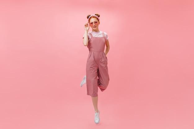 ピンクのジャンプスーツと孤立した背景にジャンプするアクセサリーの女性のフルレングスの写真。