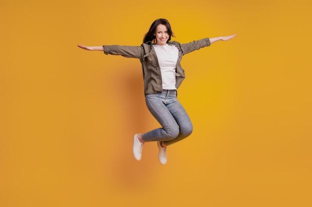 女性の完全な長さの写真は、黄色の背景の上に分離された手をジャンプジャンプを上げる