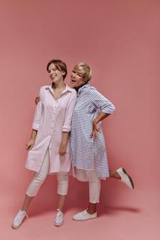 縞模様の青いロングシャツ、スキニーパンツ、スニーカーの女性の全身写真は、ピンクの背景に明るい服を着て若い女の子を笑顔で抱き締めます。