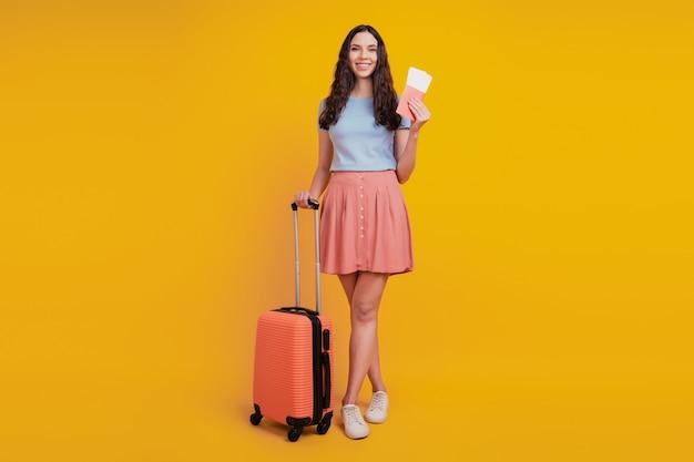 노란색 배경 위에 격리된 젊은 매력적인 여성의 행복한 긍정적인 미소 여행 가방 여행 문서 티켓의 전체 길이 사진