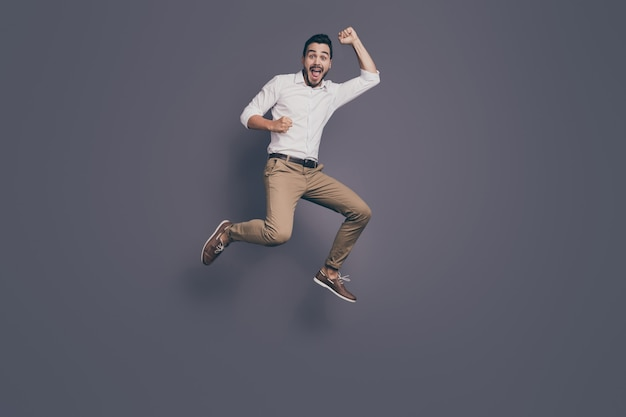 기쁨을 높이 점프 젊은 잘 생긴 비즈니스 남자의 전체 길이 사진
