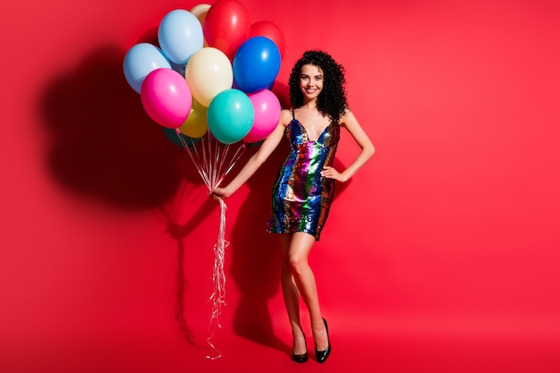 Полная длина фото молодой леди с воздушными шарами в глянцевом мини-платье на высоких каблуках, изолированных на ярком красном цветном фоне