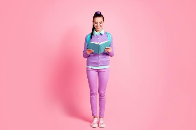 若い女性の全身写真ホールドルックブック晴れやかな笑顔着用スペックバッグバイオレットジャンパーパンツスニーカー孤立したピンク色の背景