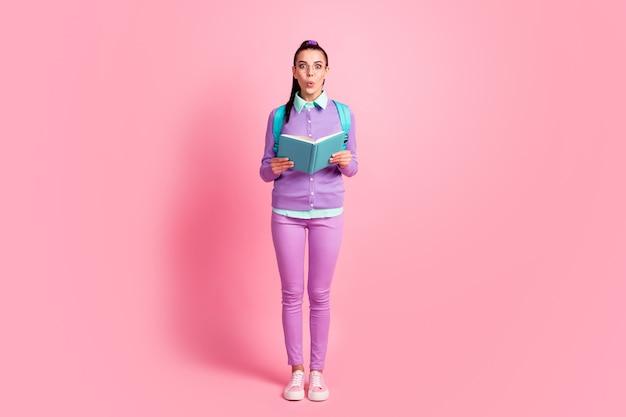 若い女性の完全な長さの写真は日記を保持しますショックウェアの仕様リュックサック紫プルオーバーパンツスニーカー孤立したピンク色の背景