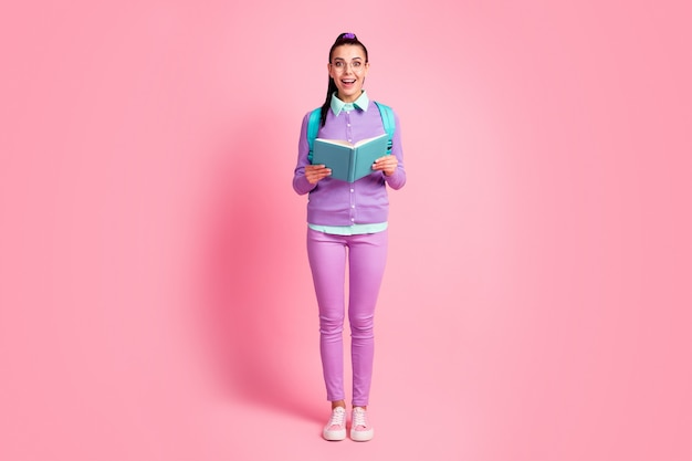 若い女性の完全な長さの写真は教科書を保持します光沢のある笑顔の着用仕様バックパック紫ジャンパーパンツスニーカー分離ピンク色の背景