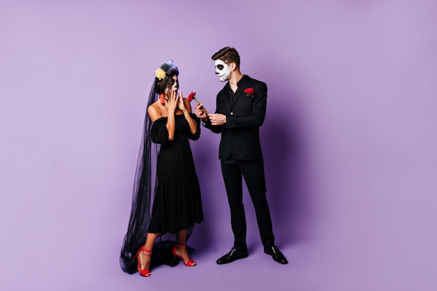 Full-length photo of pair of lovers in black outfit. man in suit gives rose to surprised girl in black veil.