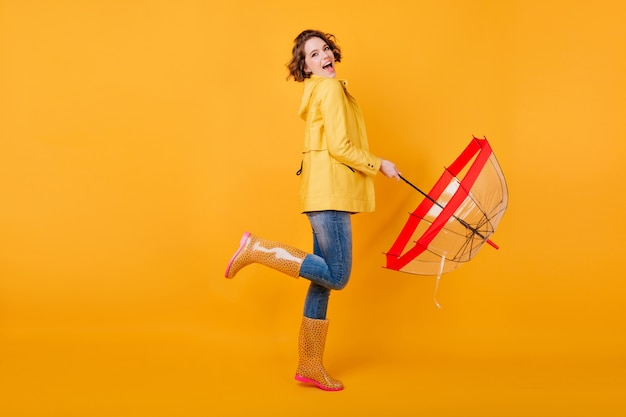Full-length photo of pleased girl in trendy autumn jacket standing on one leg. excited european female model with umbrella expressing positive emotions on yellow wall.