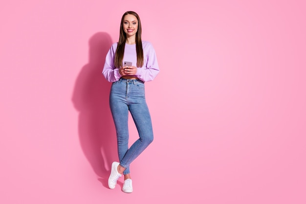 Full length photo of positive cheerful girl use cellphone enjoy social network follow post comment wear style lilac violet pullover isolated over pastel color background