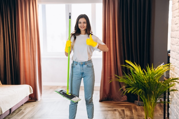 Full length photo of positive cheerful housewife wearing yellow rubber gloves enjoy washing floor hold mop feel content wearing denim jeans casual clothing in house indoors.