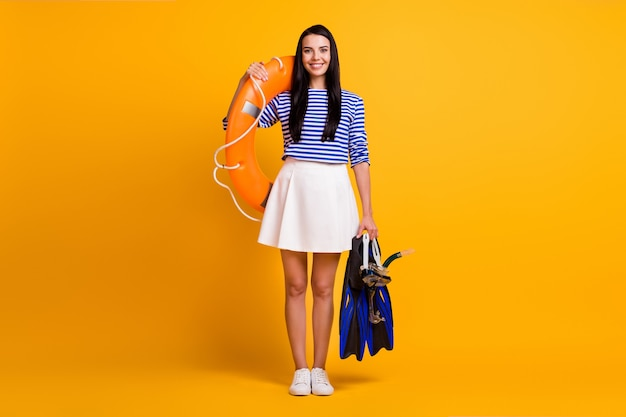 Full length photo of positive girl hold scuba diving equipment mask flippers goggles lifebuoy wear blue white skirt shirt dress sneakers isolated over bright shine color background
