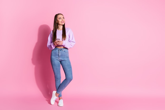 Full length photo of positive girl look copyspace use cellphone follow social media news wear lilac violet pullover isolated over pastel color background