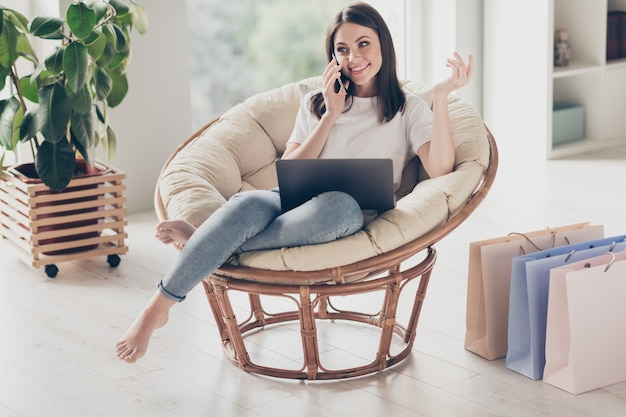 Full length photo of positive girl order purchase from online website call smartphone sit wicker chair in house indoors