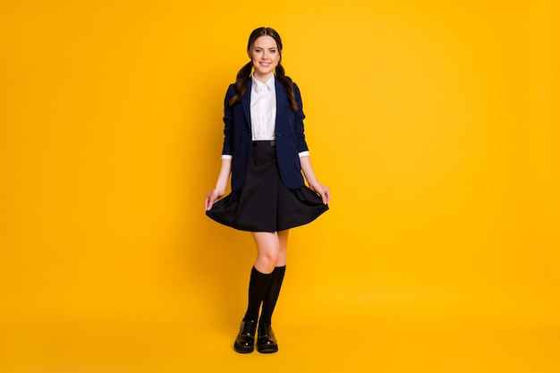 Full length photo of positive nice school teenager student touch her skirt