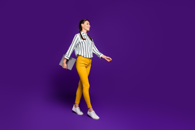 Full length photo of pretty business lady freelancer holding notebook hands walking students lecture class wear striped shirt yellow trousers isolated purple color background