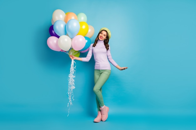 Full length photo of pretty funny lady bring many colorful air balloons friends event party wear purple sweater beret cap green pants footwear isolated blue color wall