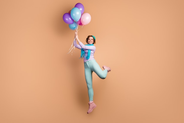 Full length photo of pretty funny lady jump high hold many air balloons raise up with wind blowing wear purple jumper green pants boots blue beret scarf isolated beige color background