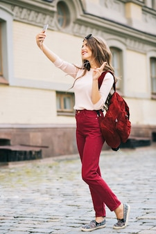 Full-length photo of pretty girl with long hair making selfie-portrait on phone in city. she has vinous color on clothes and looks enjoyed.