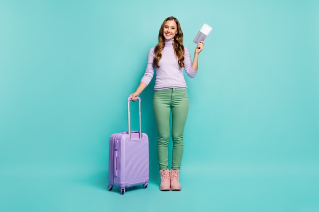 Full length photo of pretty lady airport documents registration hold tickets rolling trip suitcase wear lilac pullover green trousers footwear isolated teal pastel color