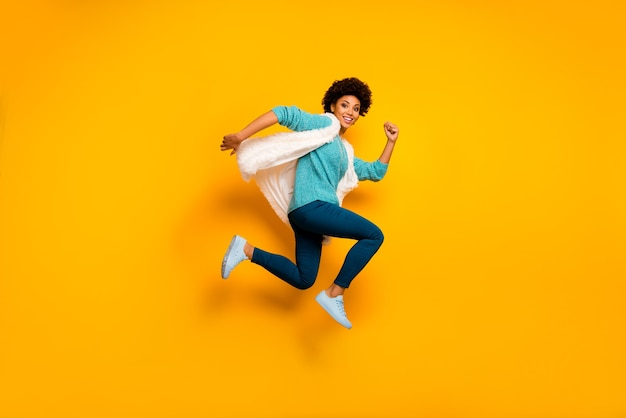 전체 길이 사진 프로필 측면 사진 펑키 미친 갈색 머리 아프리카 미국 소녀 점프 실행 판매 착용 흰색 세련 된 유행 청록색 풀오버 파란색 옷은 밝은 광택 컬러 벽 위에 절연