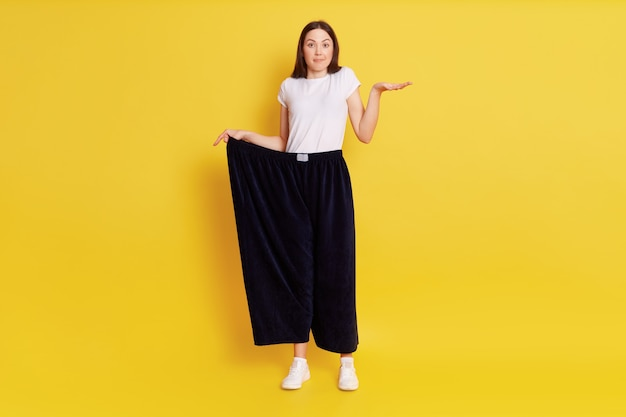 Full length photo of puzzled astonish female wearing too big blag pants, stretching palm aside, looking at camera, being surprised of loosing too much weight, posing isolated over yellow wall.