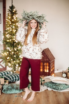 Full-length photo of a red-haired woman with a crown of fir branches posing near christmas tree