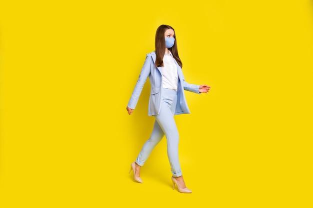 전체 길이 사진 심각한 수석 투자자는 copyspace 사무실 안전한 의료 마스크 covid 감염을 걸어 파란색 블레이저 재킷 바지 바지 하이힐 격리 밝은 광택 색상 배경을 걸어 이동