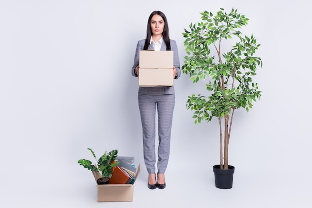 Full length photo of serious unhappy worker dismissed lady financial crisis lost work hold carton box stuff fired quit office wait courier delivery formalwear isolated grey color background