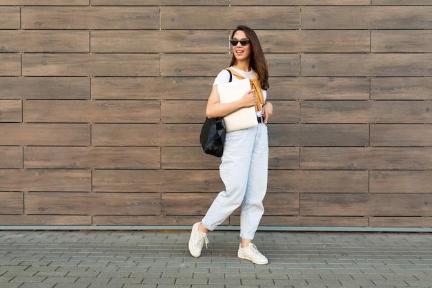 Снимок в полный рост молодой очаровательной красивой брюнетки идущей по улице возле коричневой стены