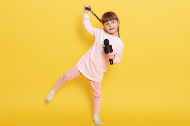 Full length photo of singing adorable caucasian girl, child performing against yellow wall, standing on one leg and touching her pigtail, expressing positive emotions, small artist arranges concert.
