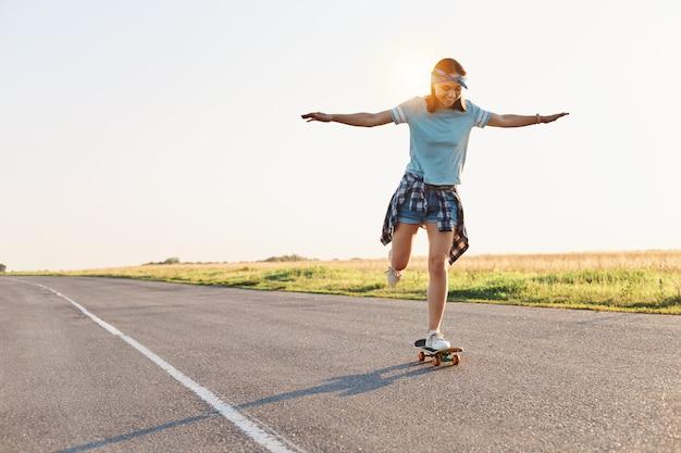 Foto a tutta lunghezza di una donna felice e attraente magra con emozioni positive e sorriso a trentadue denti, che cavalca skateboard in strada, trascorrendo l'estate in modo attivo.