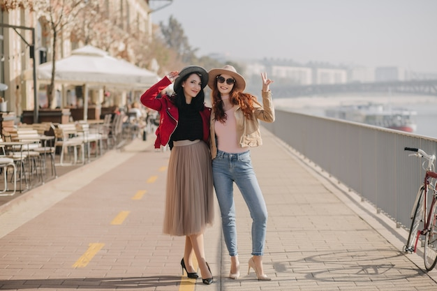 Full-length photo of slim ginger woman in casual clothes spending weekend with friend
