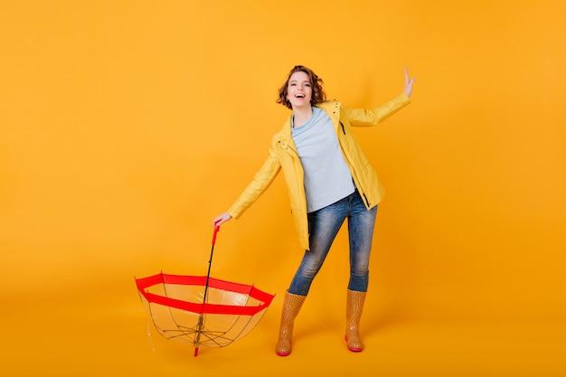 Foto a figura intera di donna sottile in abito autunnale che balla in scarpe di gomma. attraente ragazza con capelli ondulati scherzare dopo la pioggia.
