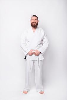 Full length photo of sport man in taekwondo uniform standing over white wall