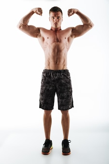 Full-length photo of strong and powerful sports man in black shorts showing his biceps