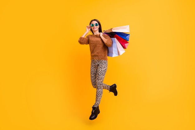 Full length photo of  stylish lady jumping high carry many shopping bags