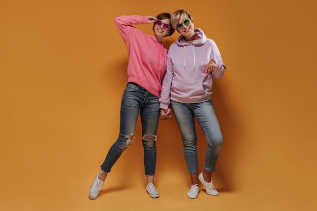 Foto a figura intera di due donne moderne in occhiali da sole luminosi, fantastiche felpe con cappuccio, jeans attillati e scarpe da ginnastica che sorridono e si tengono per mano su sfondo arancione.