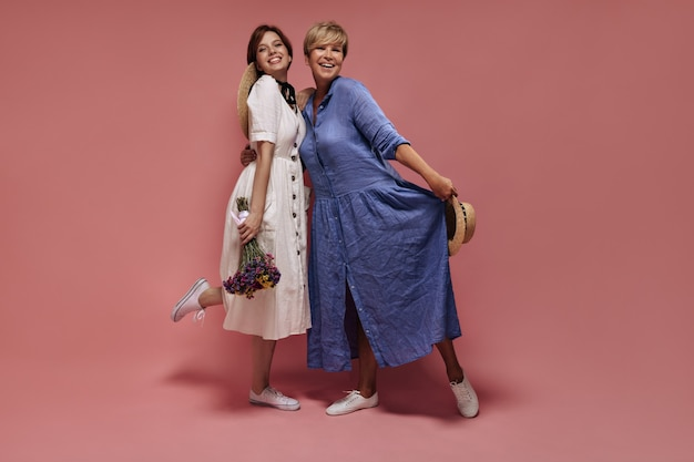 Full length photo of two women with short hair and straw hats in midi dresses and white sneakers smiling and posing with bouquet on isolated backdrop.