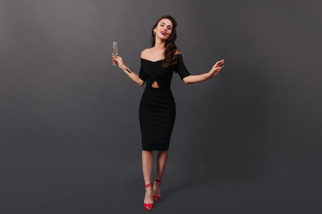 Full-length photo of woman in black fitting dress and in high heels posing on black background with glass of champagne in her hands.