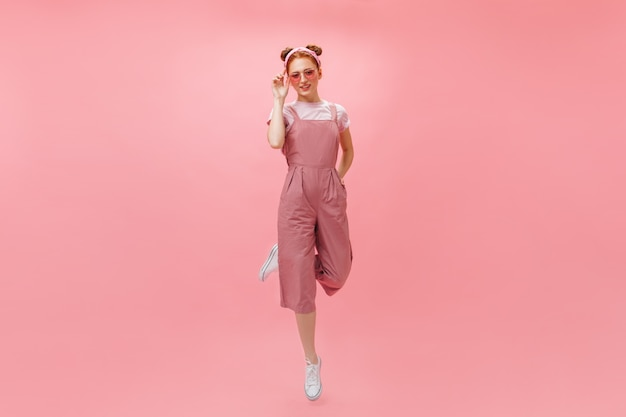 Full-length photo of woman in pink jumpsuit and accessories jumping on isolated background.