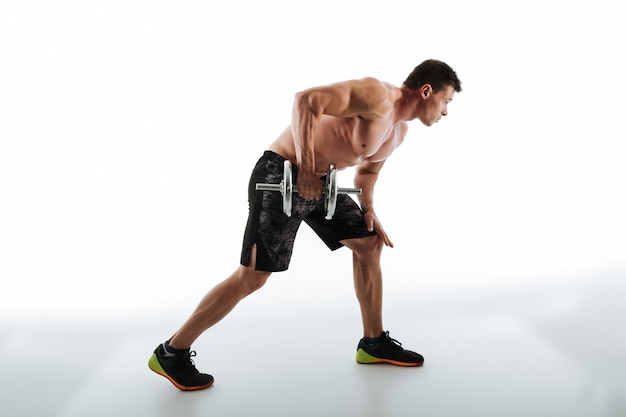 Full length photo of young attractive muscular man workout with dumbbell