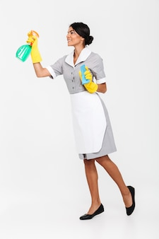 Full length photo of young brunette mais in uniform and yellow protective gloves spraying the cleaner on window