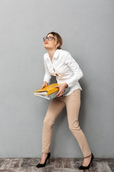 Full length photo of young businesswoman wearing glasses holding paper folders in the office, isolated