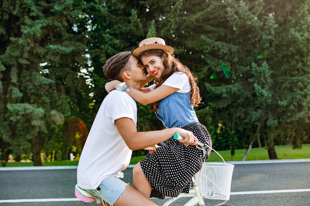 Full-length photo of young couple in love on bike on road on forest background. a guy in white t-shirt is driving a bike and kissing a girl sitting on the handlebar