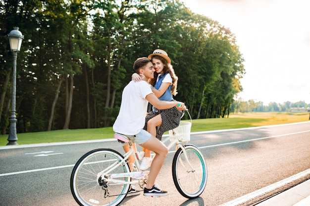Full-length photo of young couple in love on bike on road. a guy in white t-shirt is driving a bike and kissing a girl sitting on the handlebar
