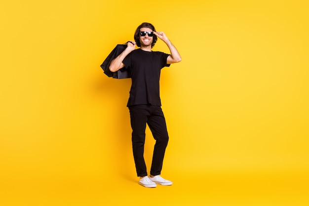 Full length photo of young man hold shopping packages glasses wear black t-shirt pants white sneakers sunglass isolated yellow color background